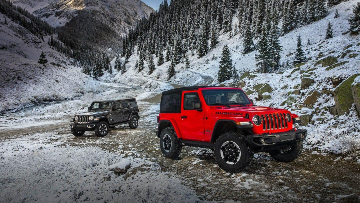 Red Jeep Wrangler and Black Jeep Wrangler on Snowy Mountainside