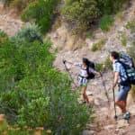 A couple walking along a hiking trail along a mountain range