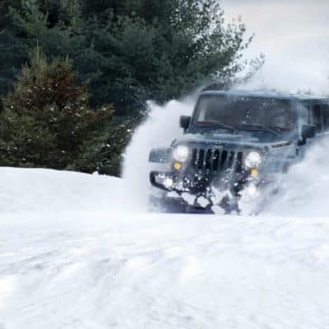 2018 Jeep Wrangler JK bounding through fresh powder