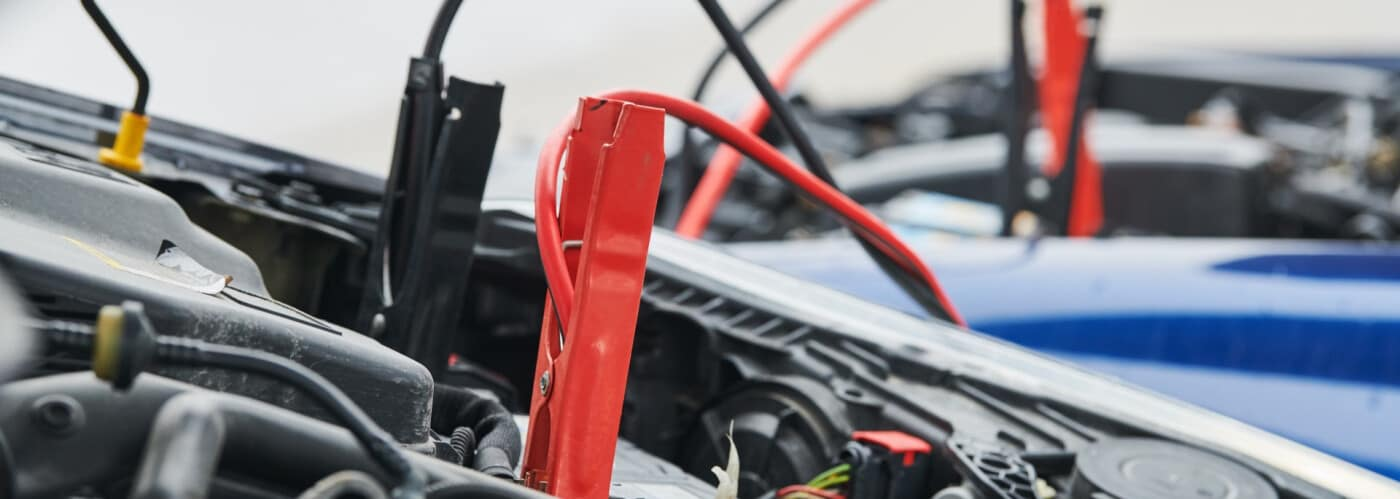 jumper cables applied to a car battery