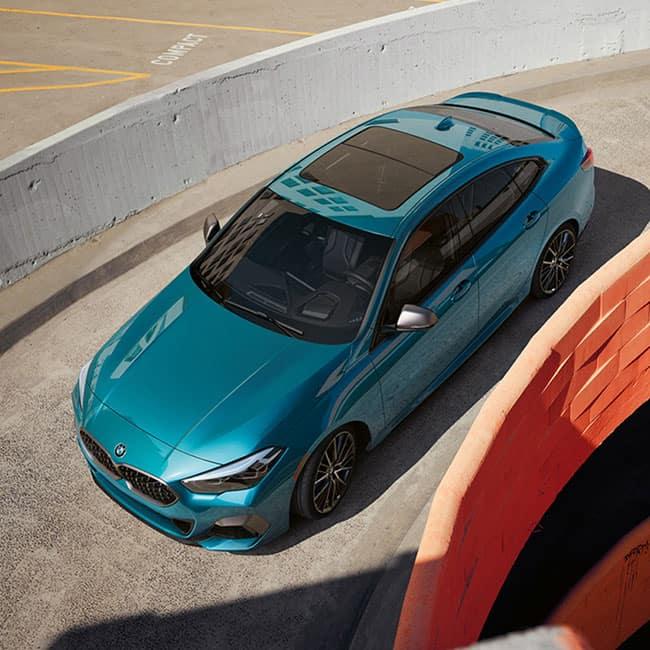 A blue metallic BMW 2 Series Gran Coupe driving down parking garage ramp.