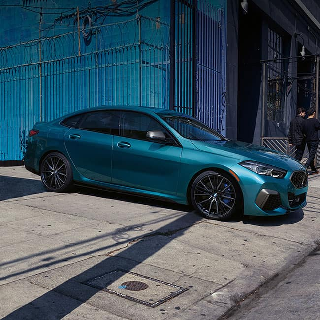 A blue metallic BMW 2 Series Gran Coupe pulling out of alley.