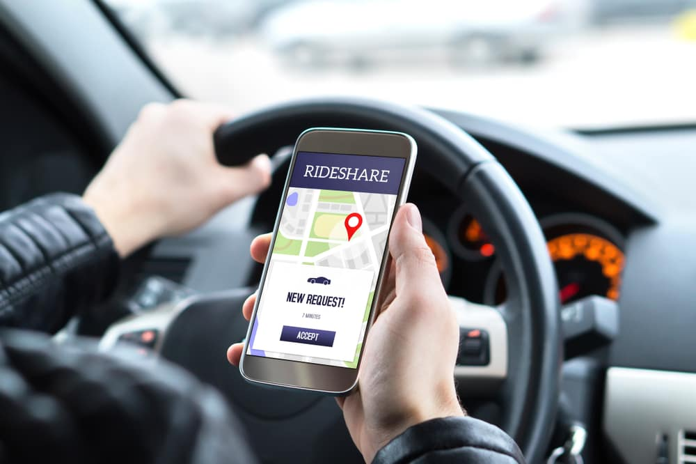 Man holding phone with a rideshare request