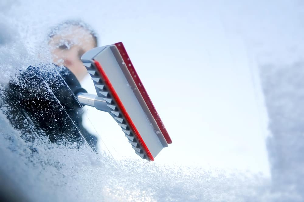 Person scraping ice and snow off of a windshield