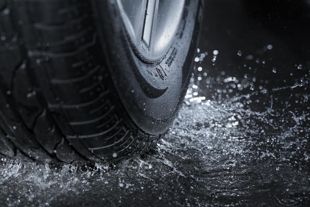 Car tire splashing water on pavement