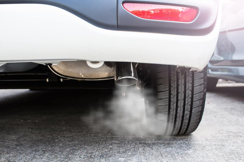 exhaust pipe on car emitting carbon dioxide and greenhouse gases