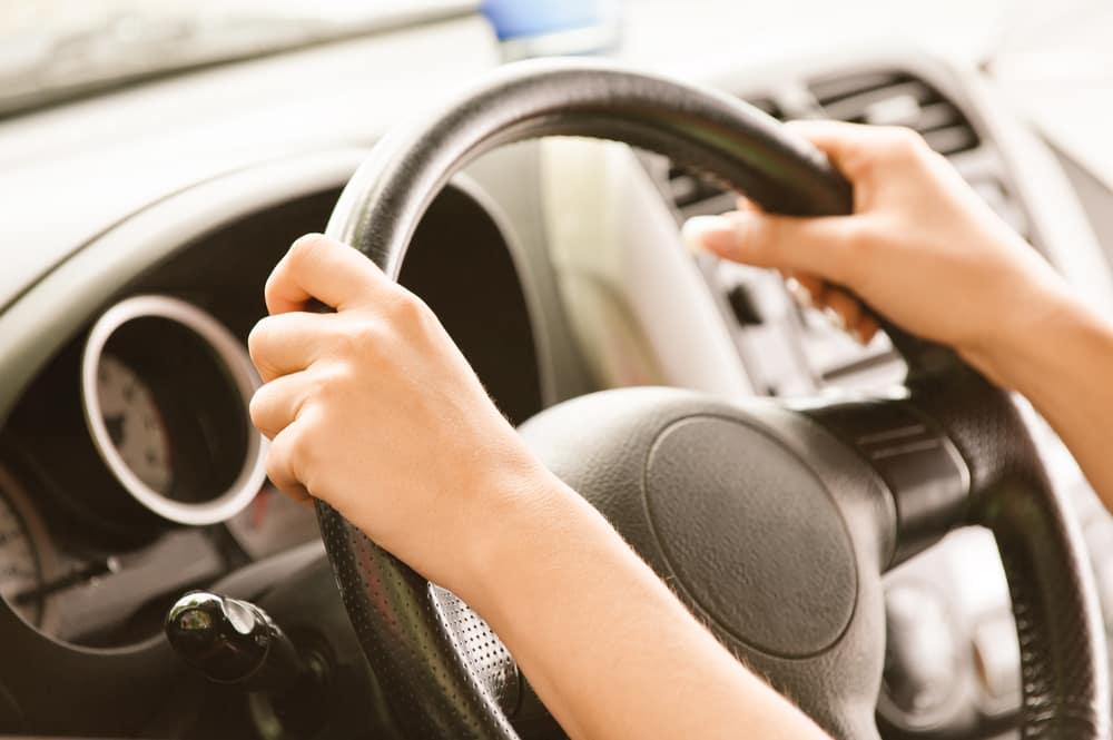 teenager's hands on a car steering wheel