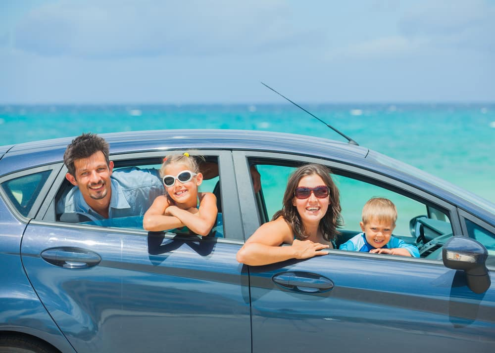 Happy family on vacation at the beach in a car