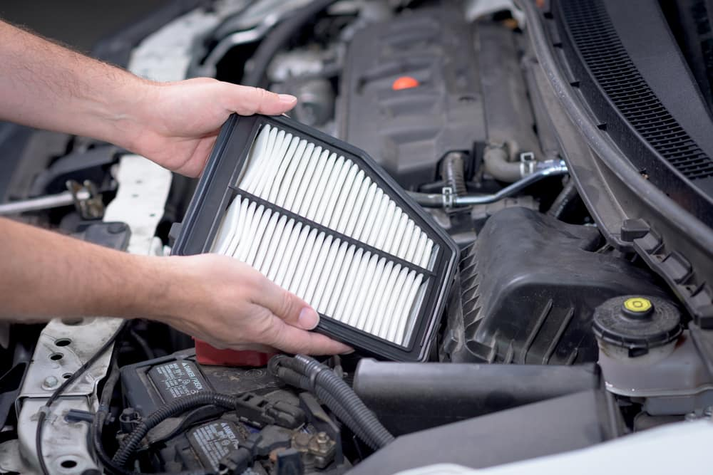 Man's hands holding an engine air filter above an engine compartment