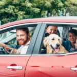 Happy family in red car after car maintenance