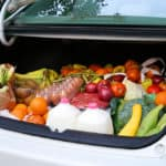 Lots of fresh food in the trunk of a car