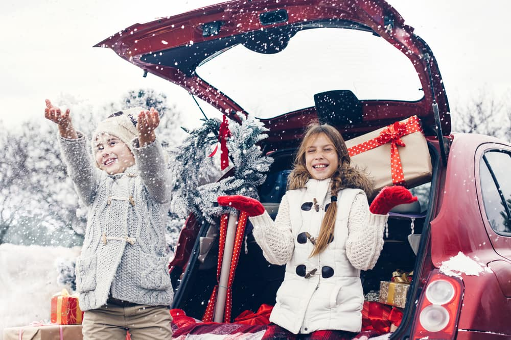 Two girls travel with Christmas presents in the trunk of their car