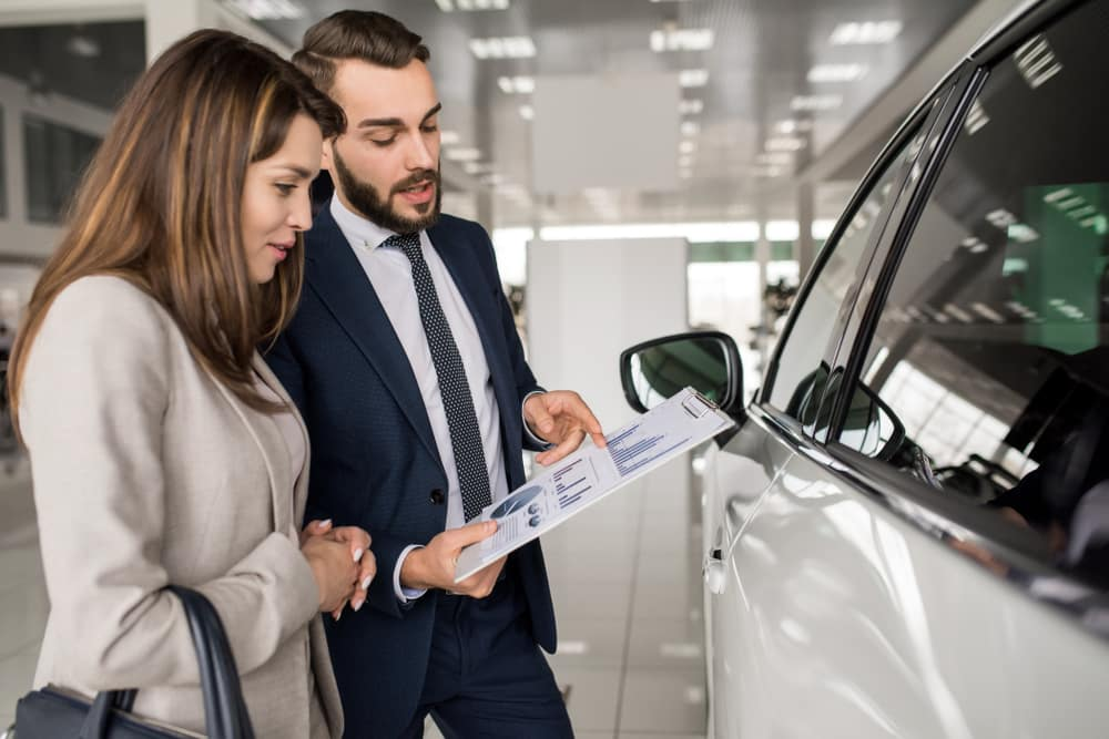 Young woman listening to a car salesman