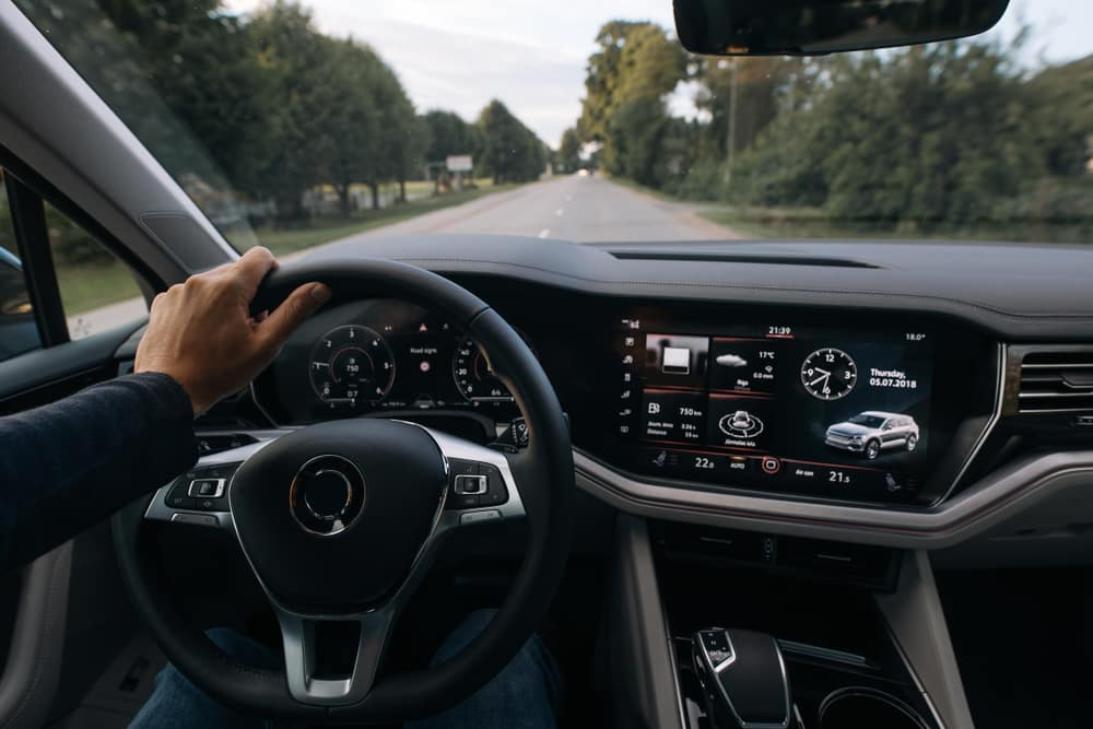 Man driving modern new SUV with hand on steering wheel
