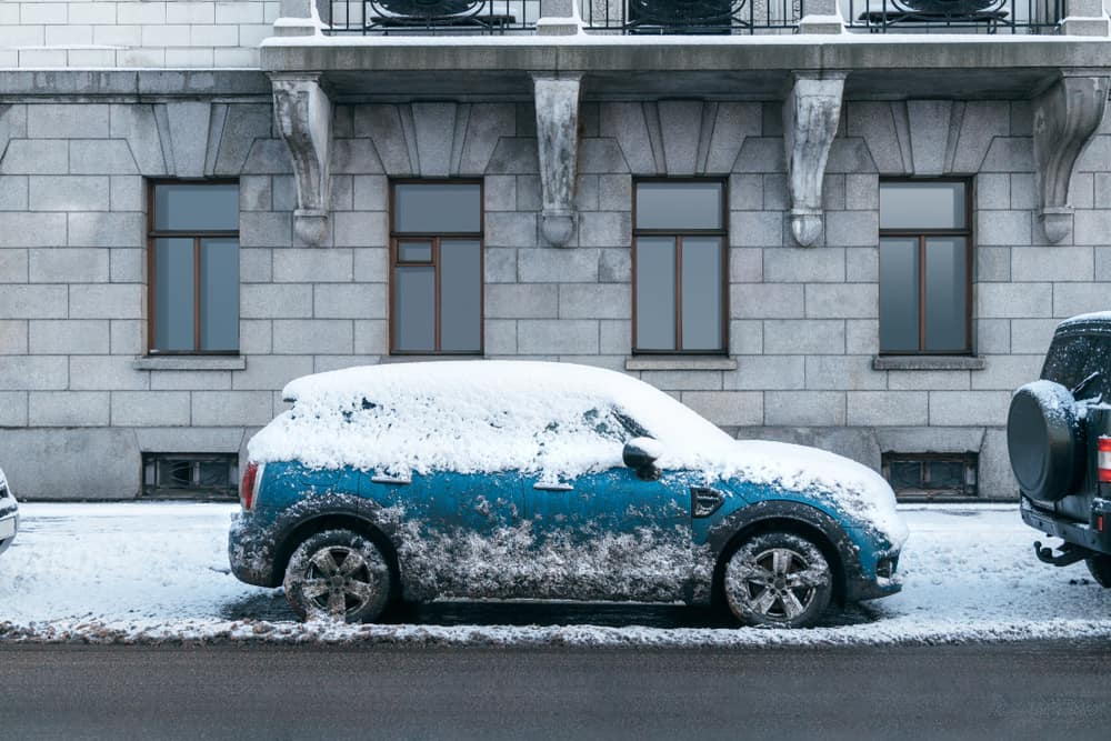 Blue car covered in snow parked in front of a stone building
