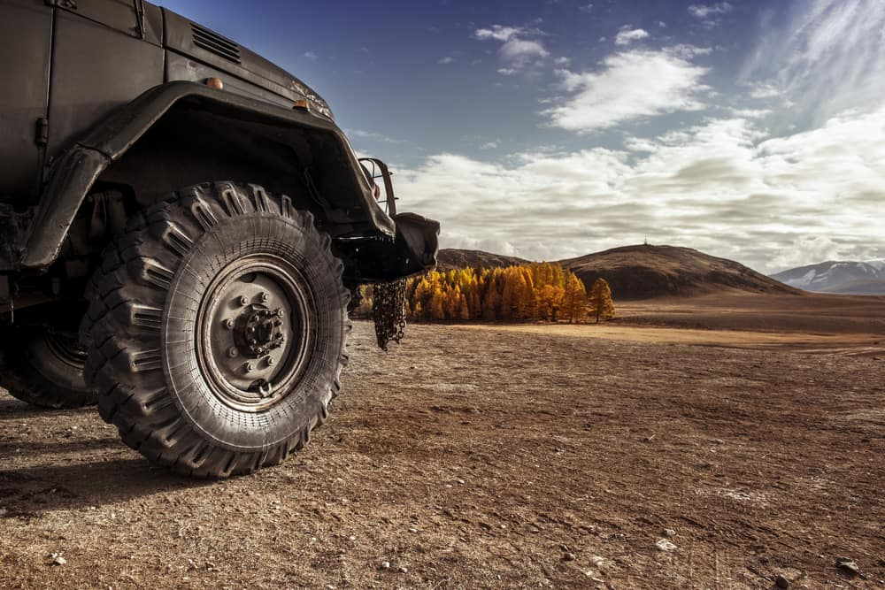 Off-road vehicle view of a tire in a dry wilderness