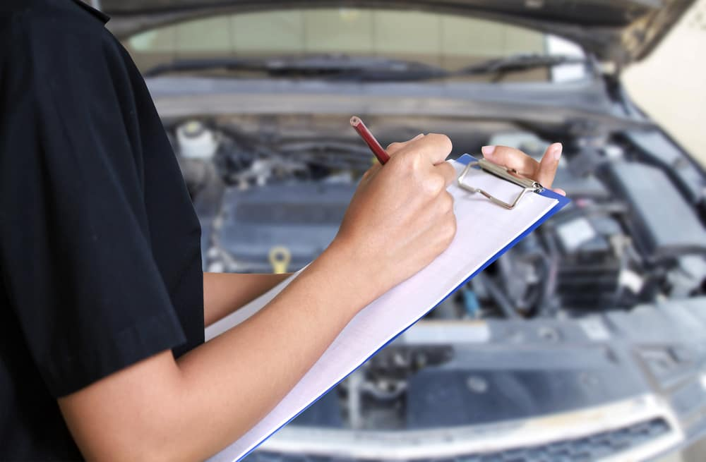 Young woman with a clipboard inspecting a car
