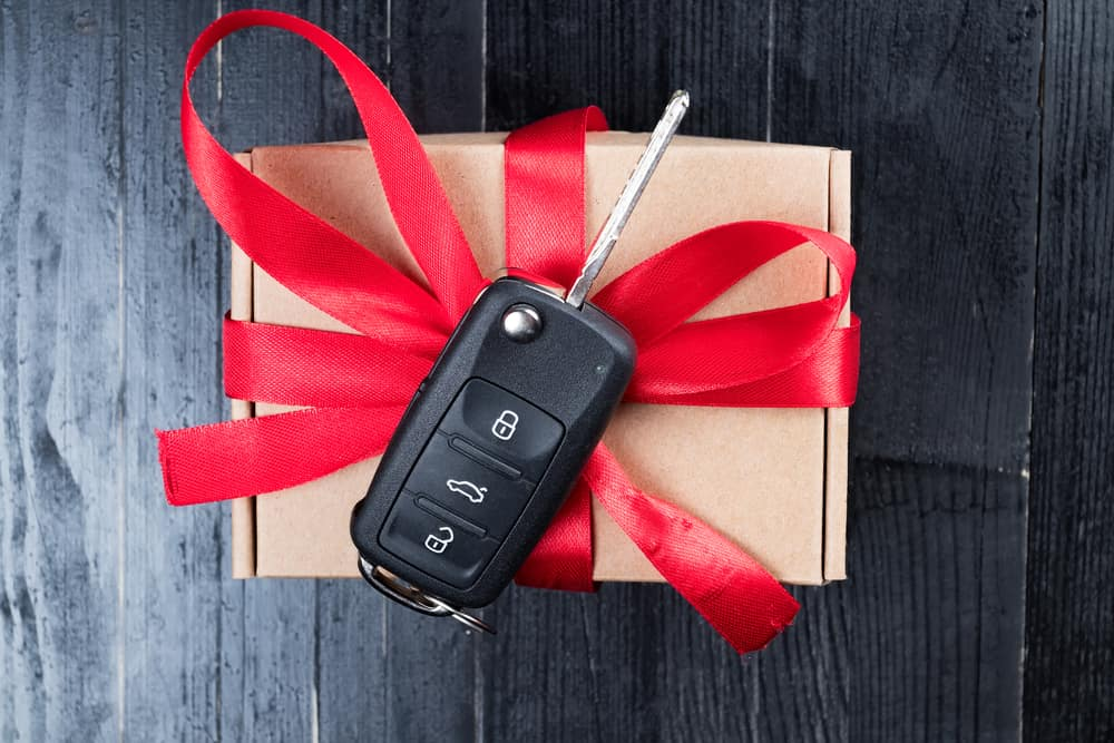 Wooden box wrapped in red ribbon with car starter on top