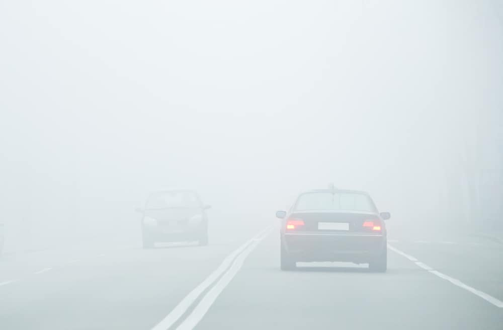 Two cars driving in fog on a two-lane road