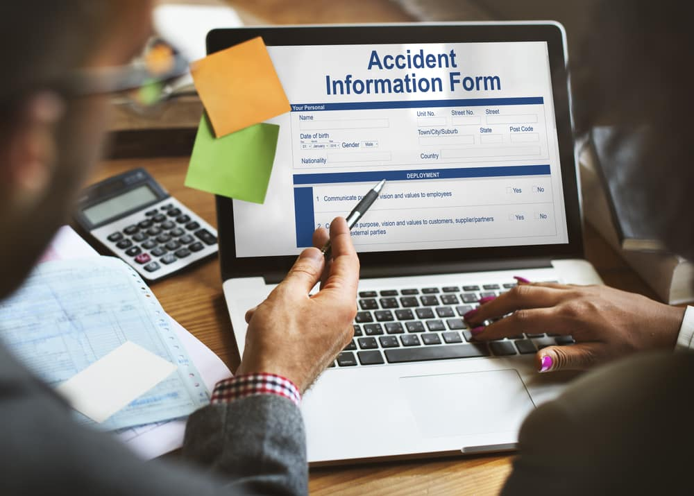 People Reviewing an Accident Report for a Used Car