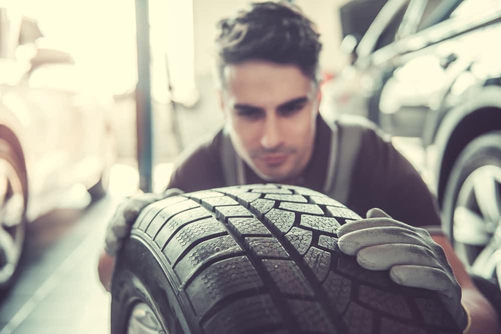Man Looking at a Car Tire