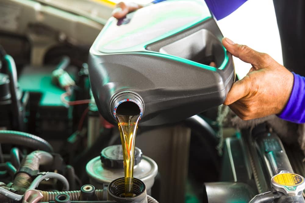Mechanic Adding Oil to an Engine
