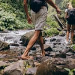 Two People Hiking Near a Stream