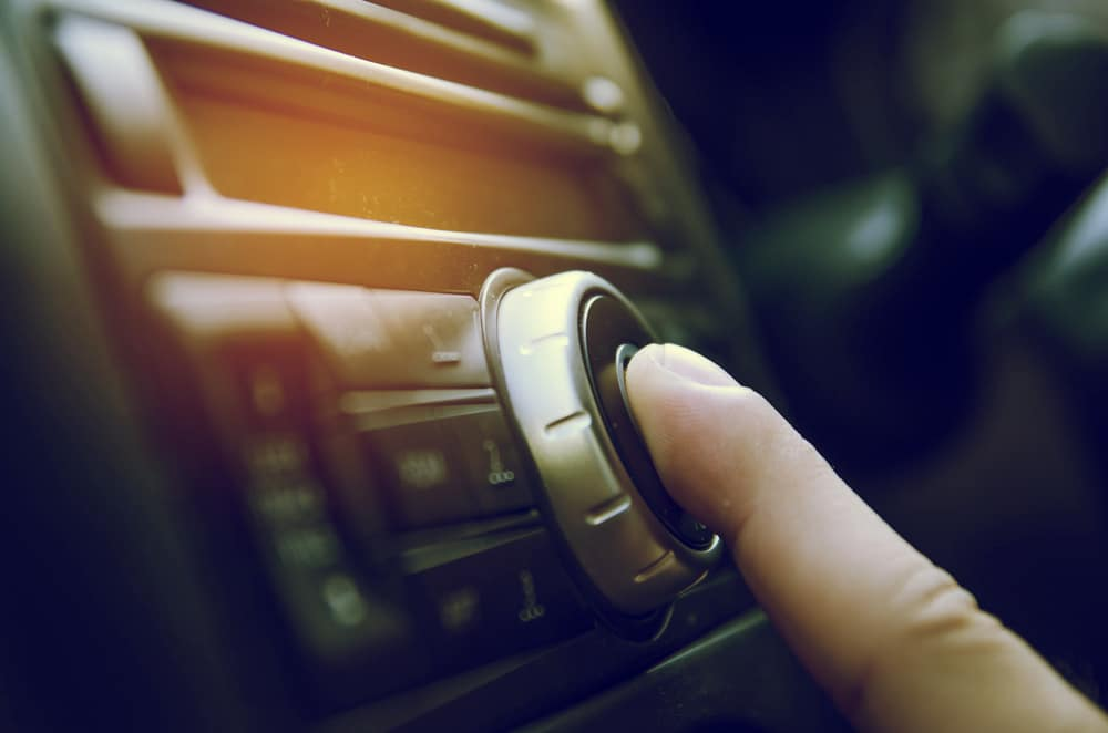 Finger pushing the button on a car stereo