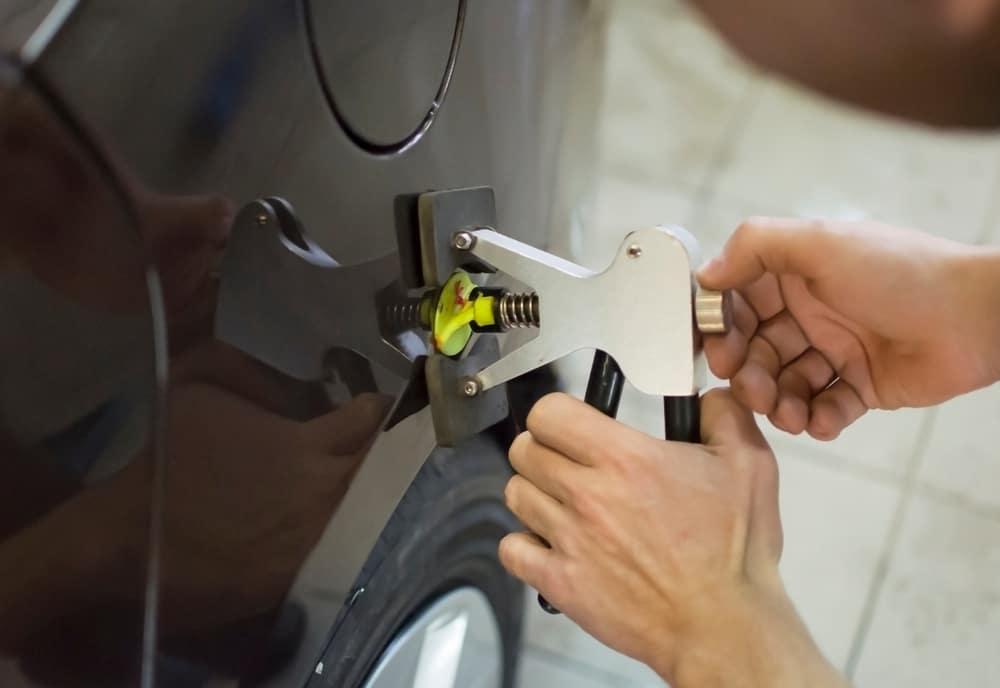 Man fixing a dent in a car fender