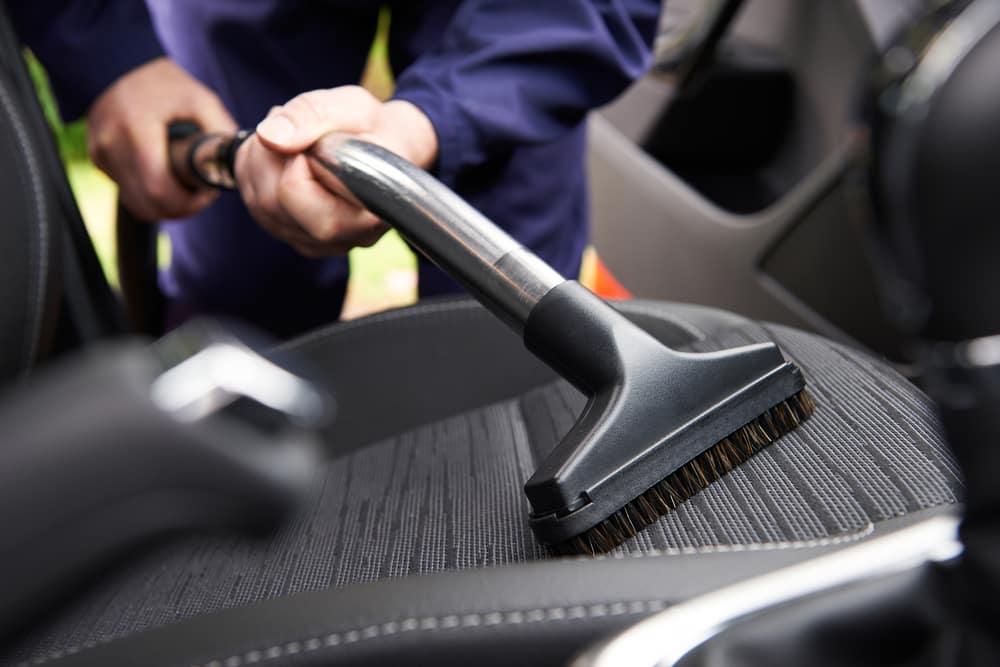 Man vacuuming a driver's seat