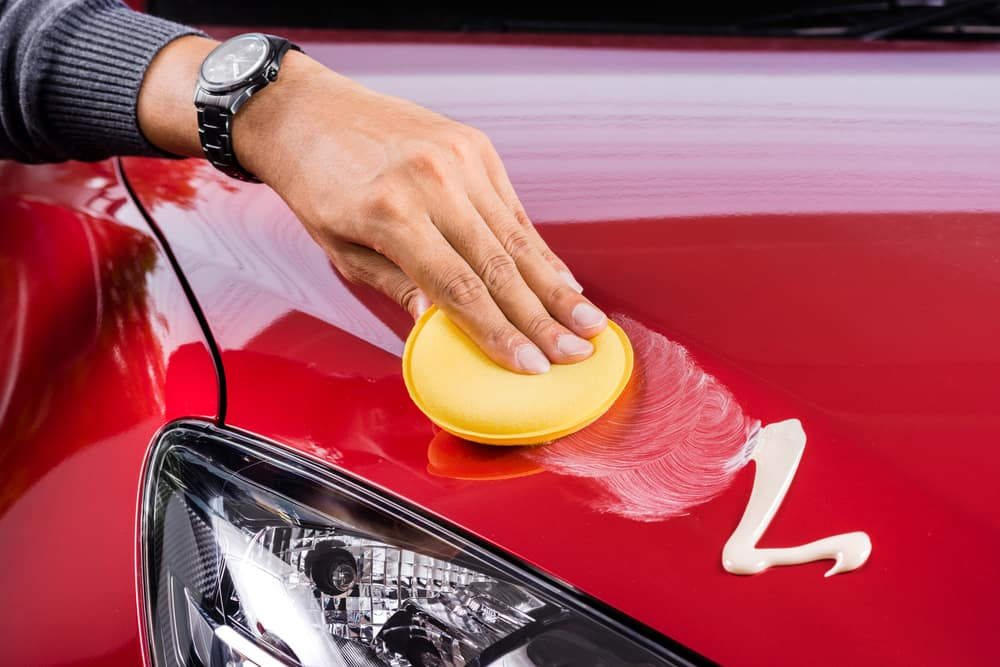 Man's hand waxing the hood of a car