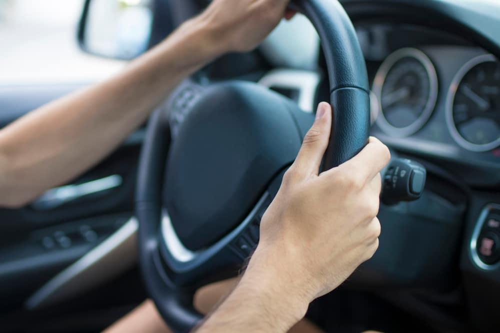 Man's hands on steering wheel