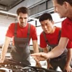 Three mechanics in red shirts fixing a car