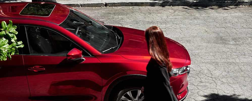 Red 2019 Mazda CX-5 Grand Touring Reserve side profile from above on street with woman walking to passenger door. 2019 Mazda CX-5 colors concept Red.