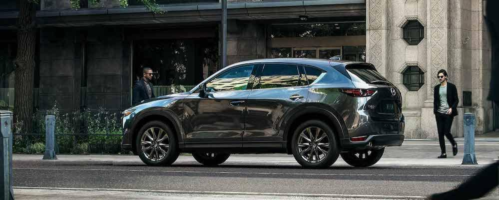 Blue Gray 2019 Mazda CX-5 Signature side profile on street with people walking by