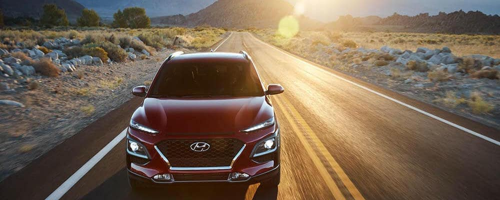 Angle on red 2019 Hyundai Kona driving on desert road with sun rays in camera lens