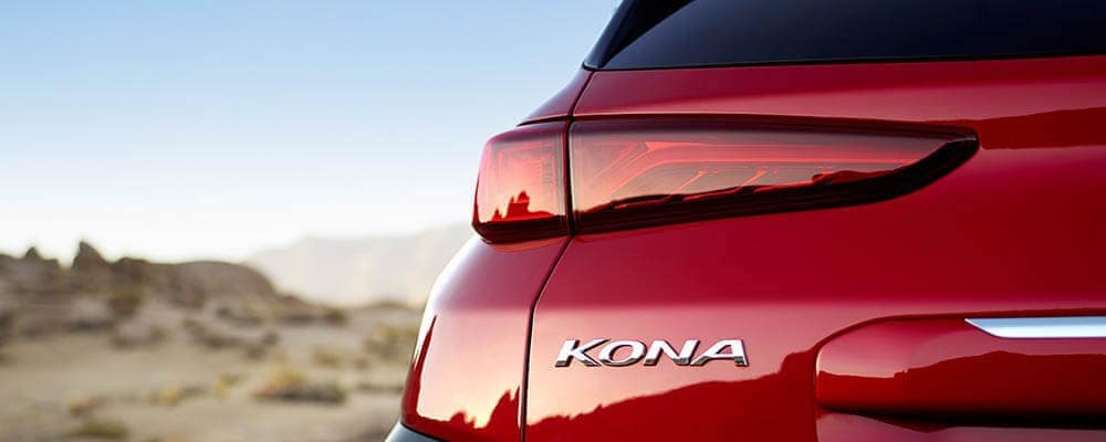 Closeup of rear left side of Pulse Red 2019 Hyundai Kona in desert