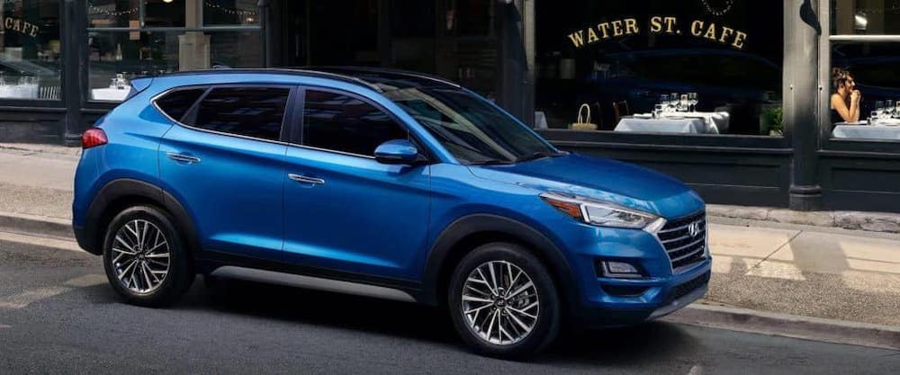 Blue 2019 Hyundai Tucson parked on city street with cafe in background