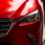 Close on front grille of red 2019 Mazda CX-3 with woman waling up to driver's side door