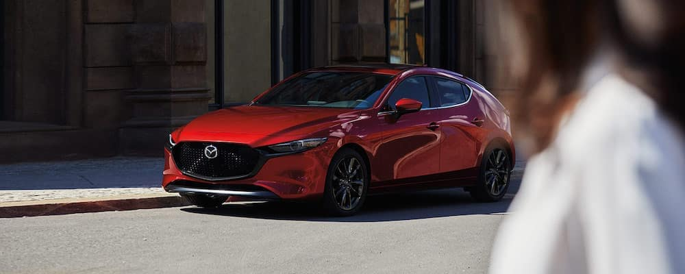 Red 2020 Mazda3 on street with blurred person in white shirt in foreground