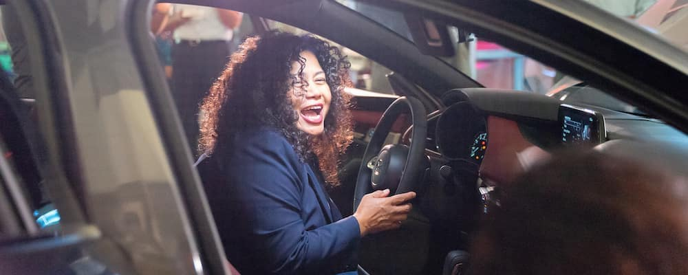Woman smiling while siting inside 2020 Mazda3 at Triple J Guam