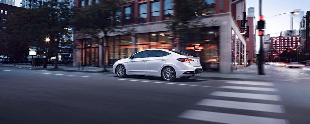 White 2020 Hyundai Elantra driving on city streets with blurred buildings in background