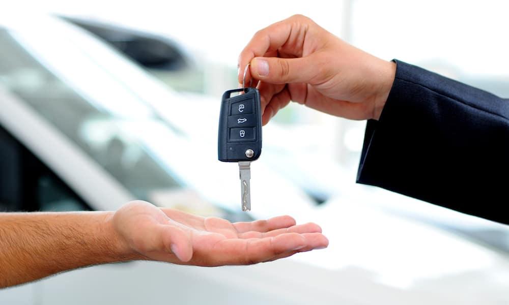 Handing Key to Man at Dealership