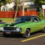 Green 1971 GMC Sprint convertible with black racing stripes in parking spot