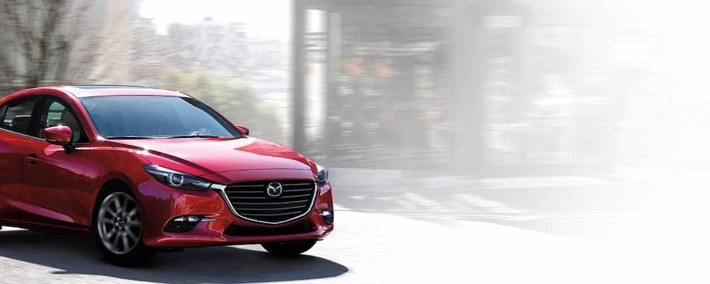 Red 2018 Mazda3 rounding a corner on a city street