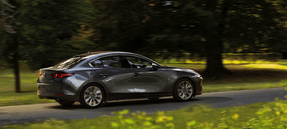 2019 Mazda3 driving down tree-lined street
