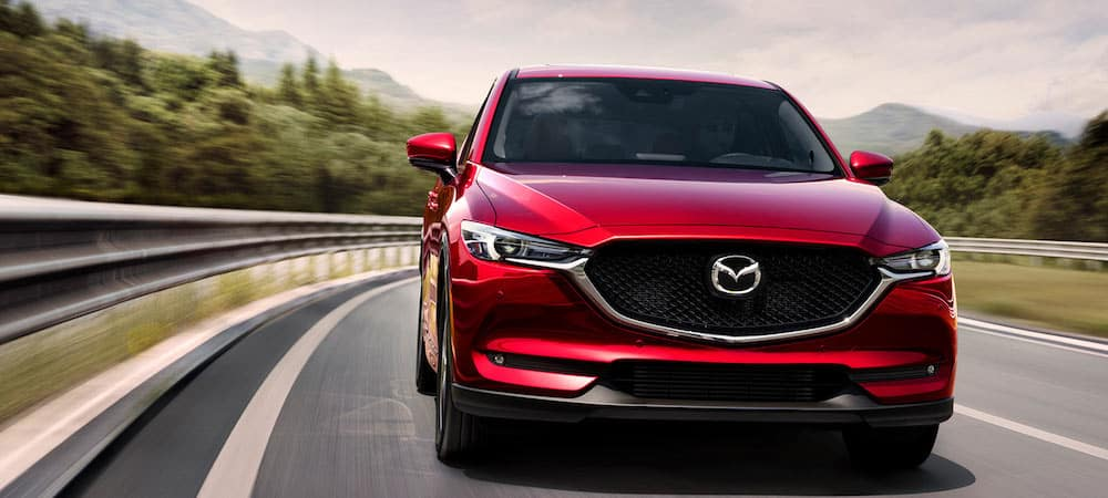 Red Mazda CX-5 cruising down tree-lined highway