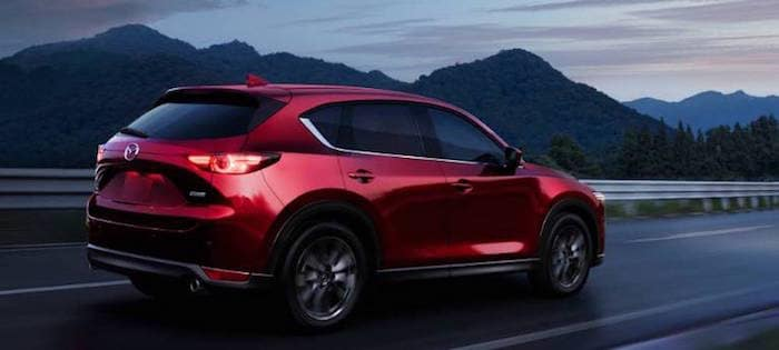 Red Mazda CX-5 driving along highway at dusk with mountains in the background