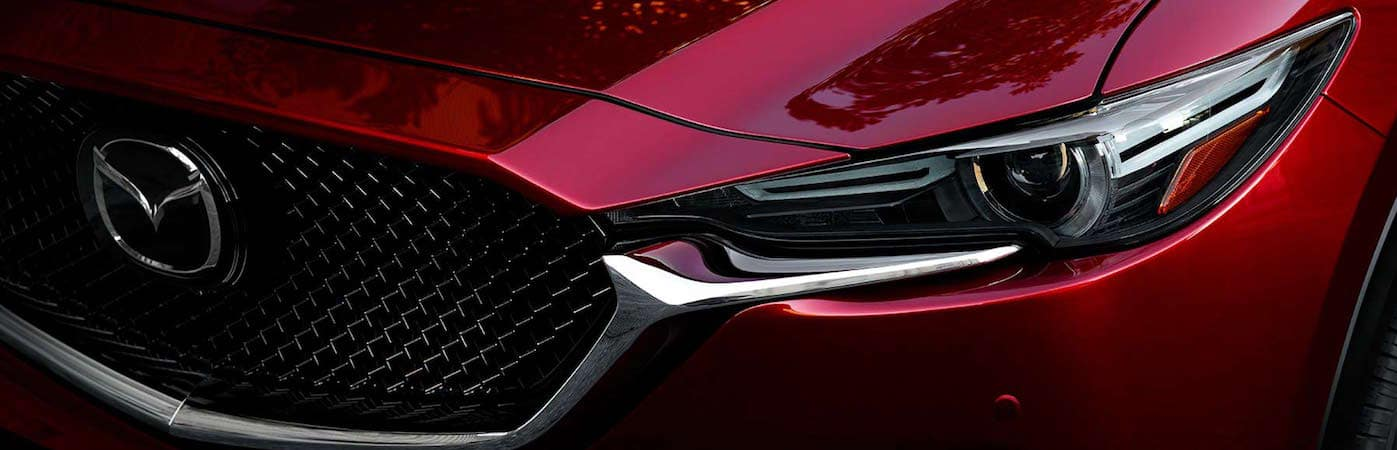 Front grille and driver's side headlight on red Mazda CX-5