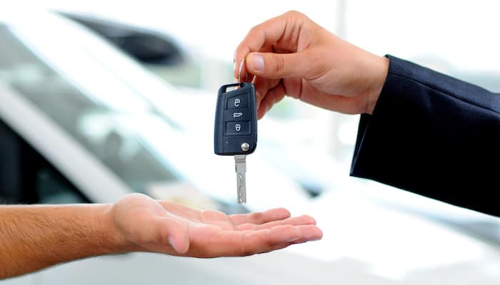 Salesperson handing car keys to new car-buyer